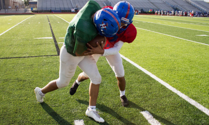 Senior Cornerback Hector Fuentes and junior Quarter- back Xavier Martinez reenact an illegal move, spearing, after their varsity practice. In an actual game, a corner- back would go after the quarterback and try to tackle to stop the play. Photo by Mya Tapia.