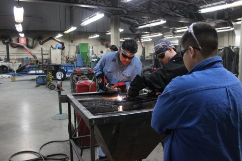 Welding students use a plasma cutter to cut a piece of metal