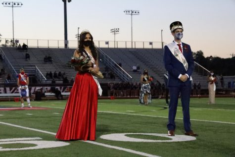 Homecoming queen Evelyn Martinez, 12, and Homecoming King Caiden Borrego, 12, face the roaring crowd at the homecoming football game against Lake Travis on Oct. 16.