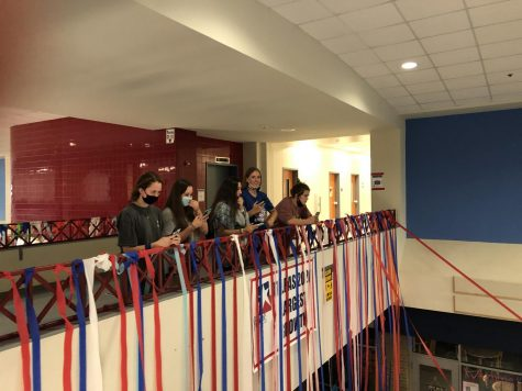 Seniors watch as Principal David Pierce enters the main hallway to witness the cup pyramids and streamers set up by seniors. The
