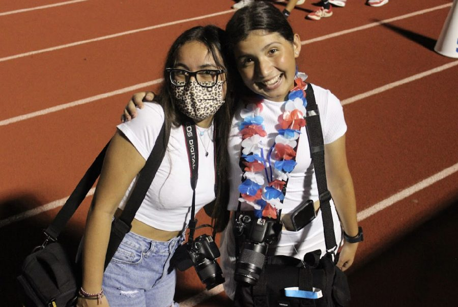 Senior yearbook editors Abi Munoz and Emma-Leigh Thurman capture images of Hays fans in the stands.